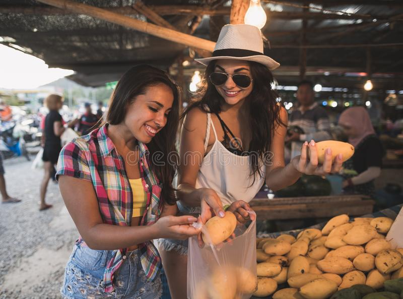 Young Women Talking While Buy Exotic Fruits On Tropical Market Happy Smiling Girld Tourists In Asian Traditional Bazaar stock images