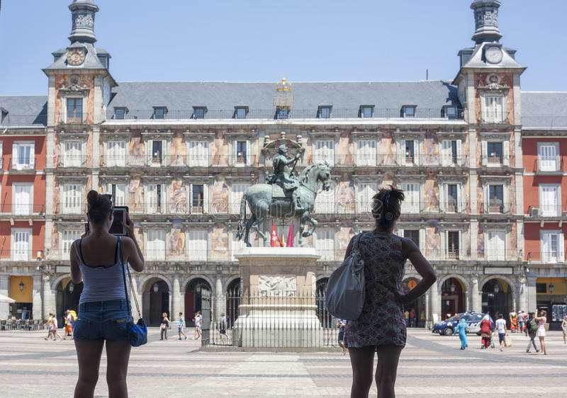 Young women tourist taking pictures in Plaza Mayor square royalty free stock image