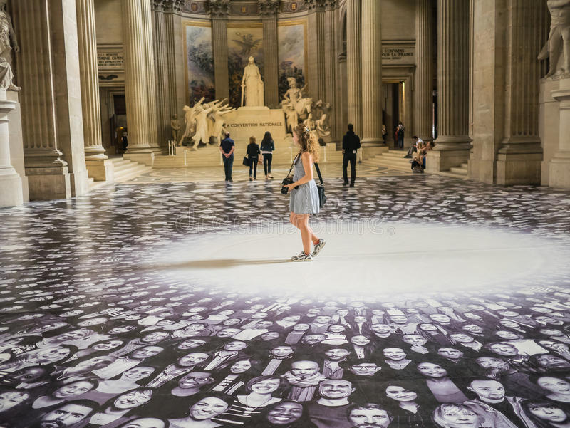 Young women tourist walks through JR display in Paris Pantheon stock image