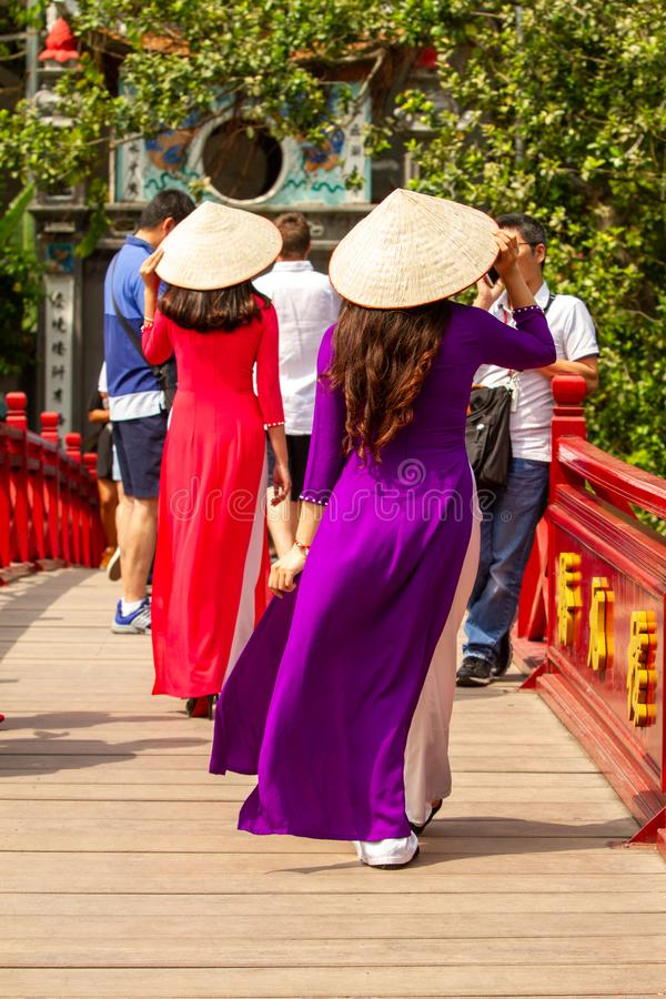 Young women in traditional dress crossing bridge to the Temple of the Jade Mountain, Hanoi, Vietnam stock images