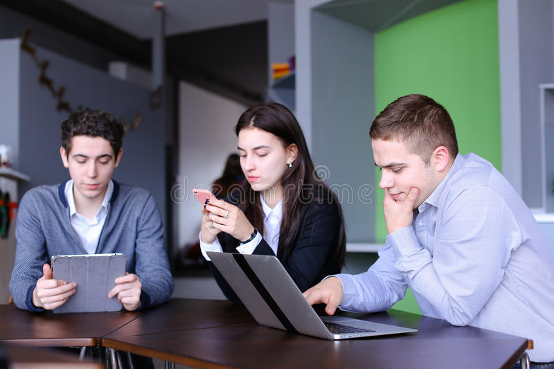 Young women and two men at lunch are busy with their own affairs stock images