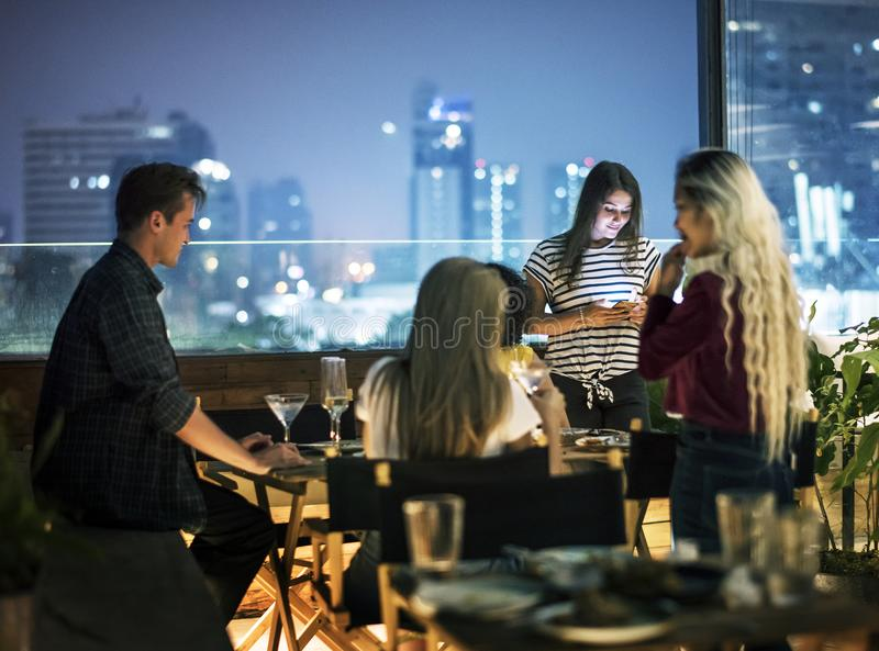 Young women using a smartphone at a dinner night having no inter stock photography