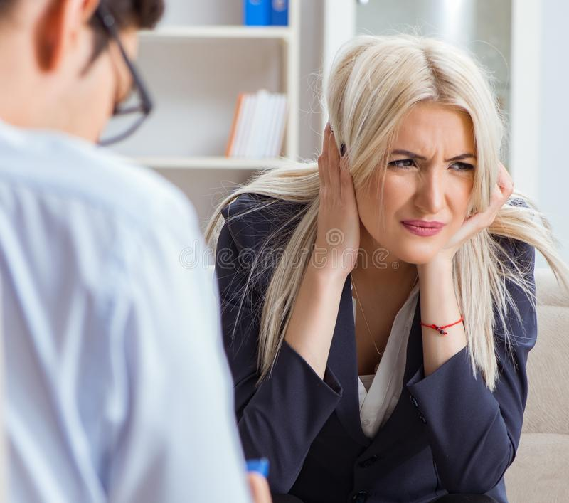 Young woman visiting psychiatrist man doctor for consultation. The young women visiting psychiatrist men doctor for consultation royalty free stock photo