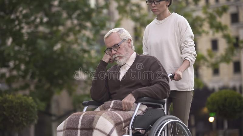Young woman on walk with sad pensioner in wheelchair, caregiver assistance, help royalty free stock images