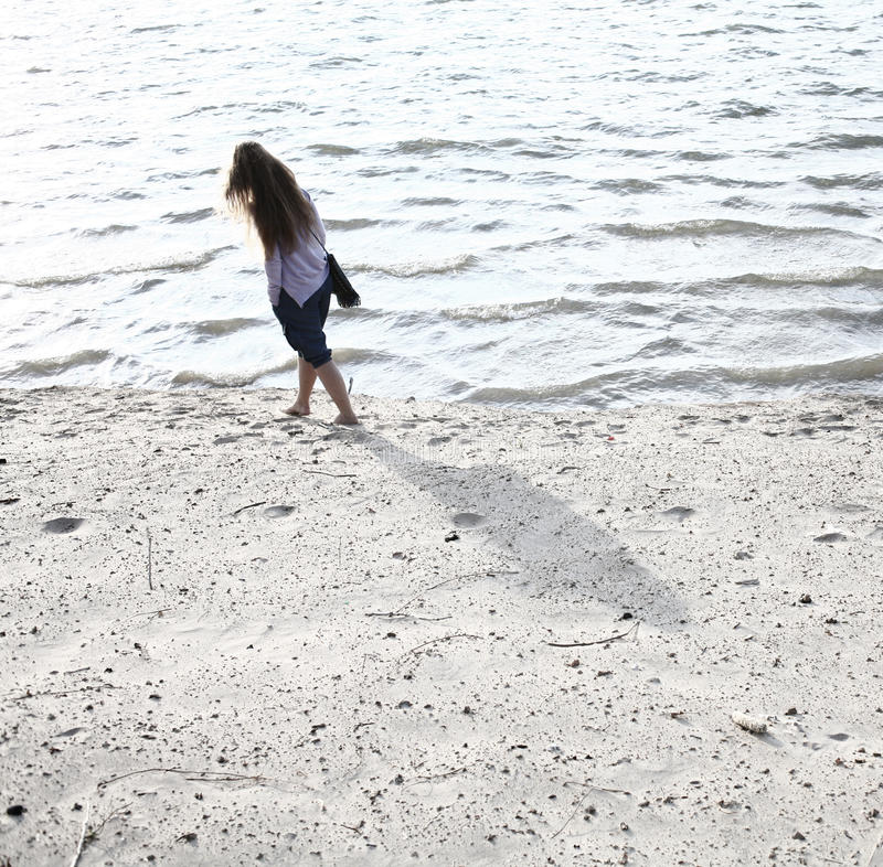 Young women walk on seashore. Full body rear shot. Young woman walking on seashore. Full body shot rear view a lot of copyspace royalty free stock photos