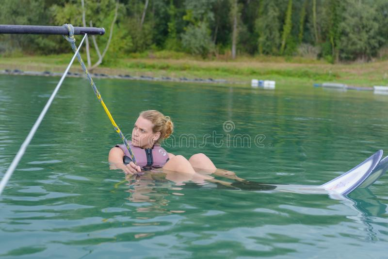 Young woman water skiing on slalom course. Young women water skiing on a slalom course stock photo