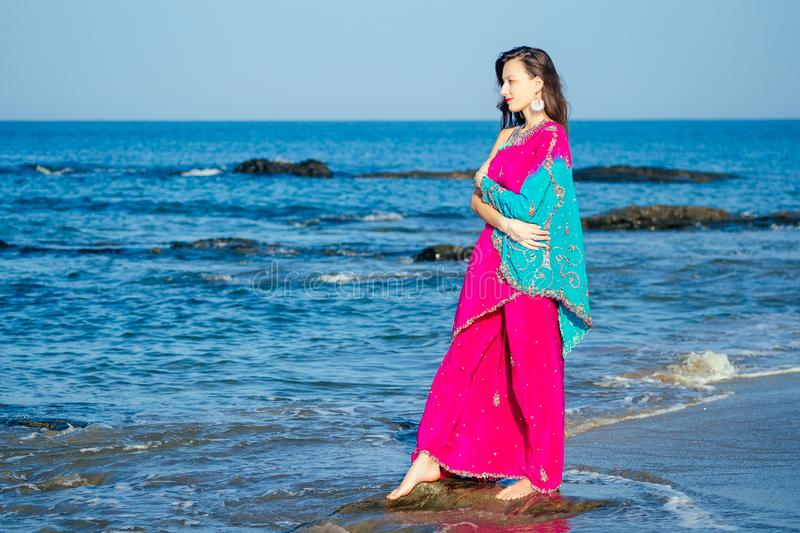 Young women wearing a pink blue saree on the beach goa India.girl in traditional indian sari on the shore of a paradise. Young woman wearing a pink blue saree on royalty free stock photography