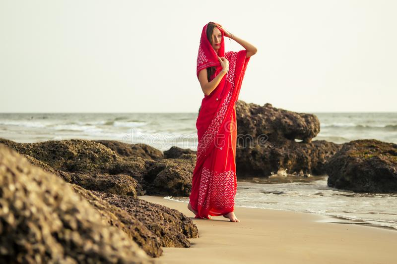Young women wearing a red saree on the beach goa India.girl in traditional indian sari on the shore of a paradise island. Young woman wearing a red saree on the stock photo