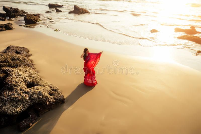 Young women wearing a red saree on the beach goa India.girl in traditional indian sari on the shore of a paradise island. Young woman wearing a red saree on the royalty free stock photo
