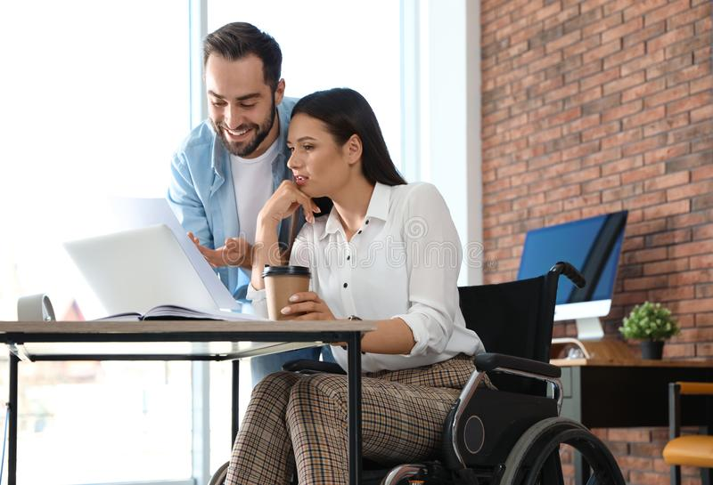 Young woman in wheelchair with colleague. Young women in wheelchair with colleague at workplace stock photography