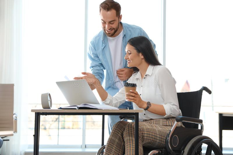 Young woman in wheelchair with colleague royalty free stock image