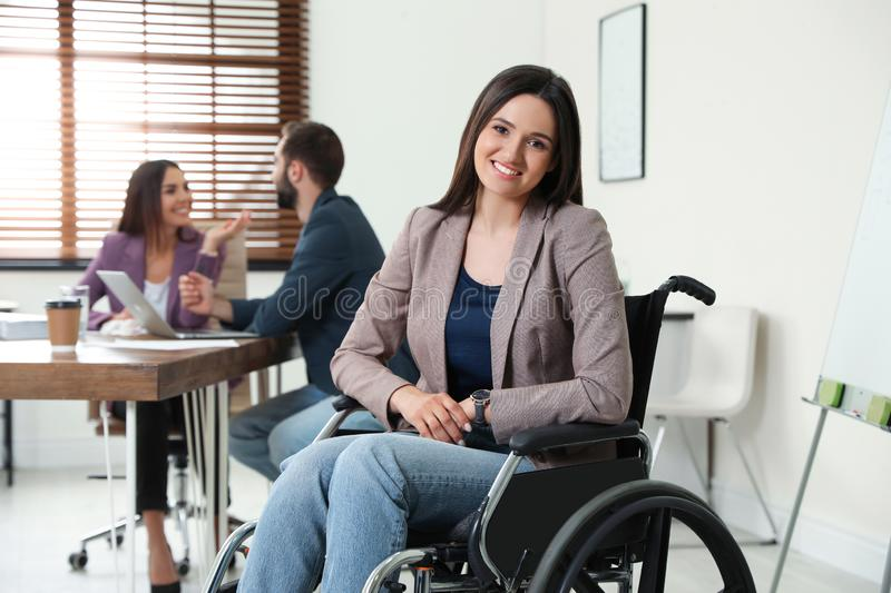 Young woman in wheelchair with colleagues royalty free stock photo