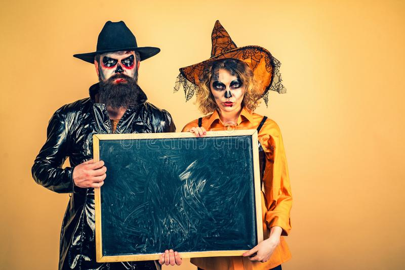 Young women witch in Halloween hat and bearded man over  background. Portrait of happy young couple in Halloween royalty free stock photos
