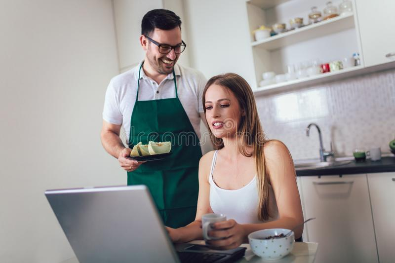 Woman working on laptop in kitchen as boyfriend prepares meal stock photos