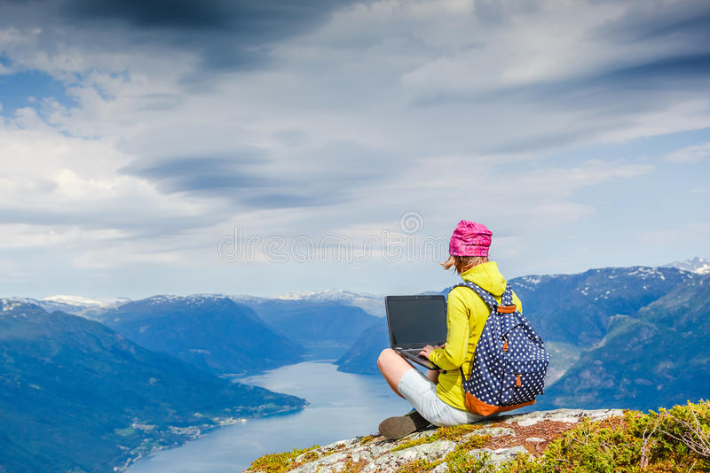 Young women working with laptop. Young woman working with laptop with beautiful nature landscape royalty free stock image