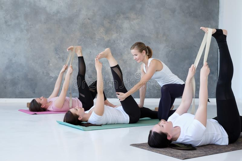 Young women working out doing exercise on floor in Supta Padangushthasana stock image
