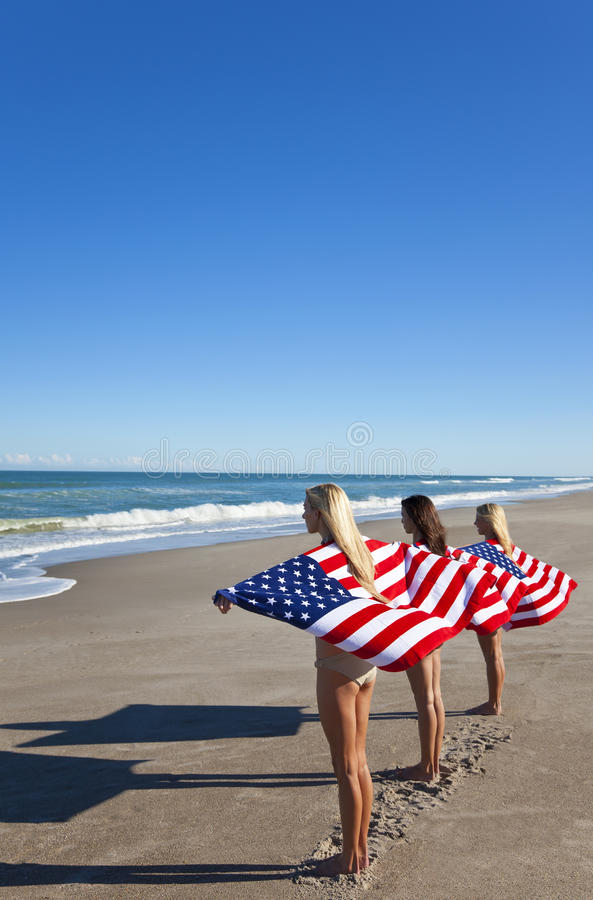 Young Women Wrapped in American Flags on a Beach stock photos