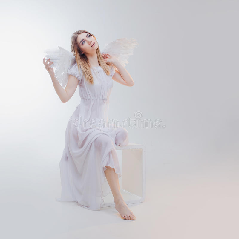 Young, wonderful blonde girl in the image of an angel with white wings. royalty free stock image