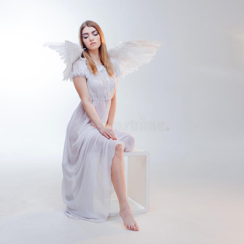Young, wonderful blonde girl in the image of an angel with white wings. royalty free stock photography