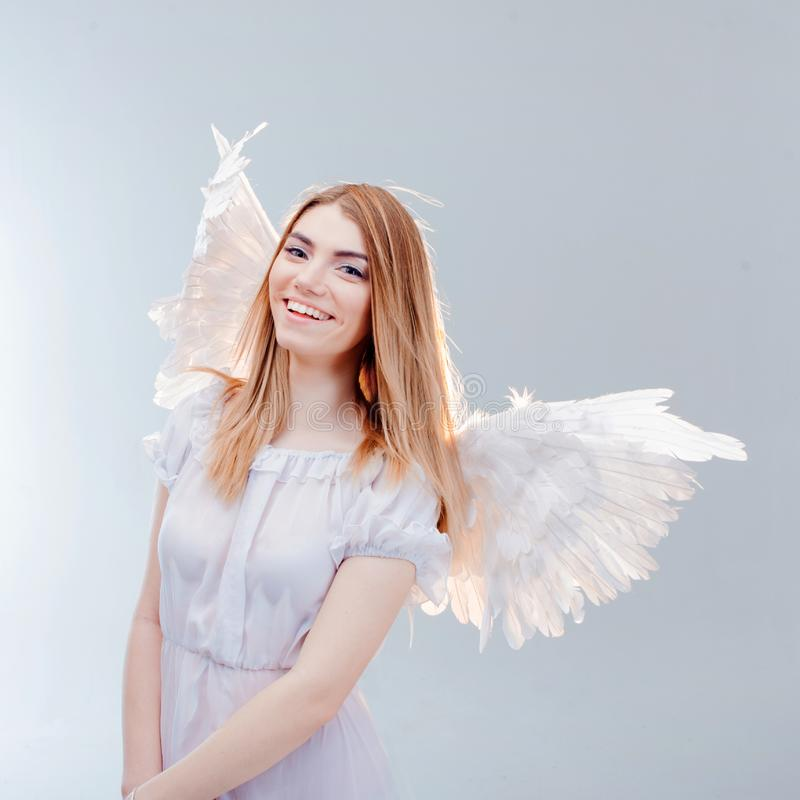 An angel from heaven. Young, wonderful blonde girl in the image of an angel with white wings. royalty free stock image