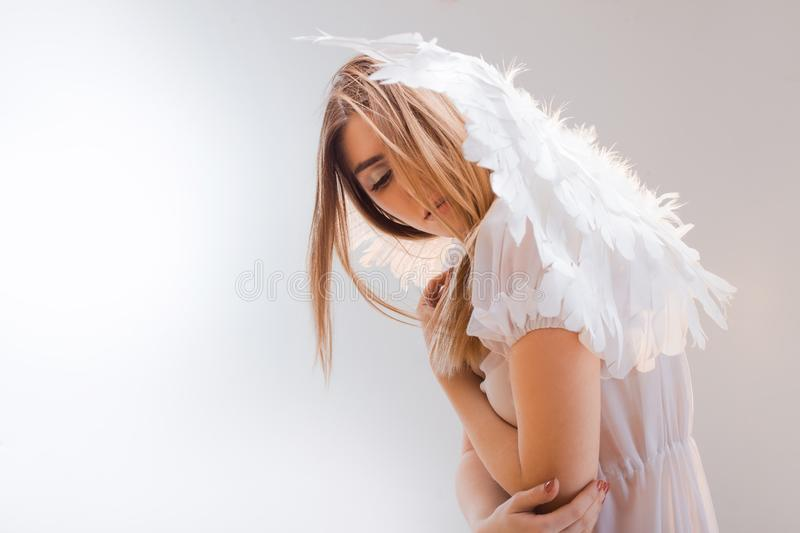 An angel from heaven. Young, wonderful blonde girl in the image of an angel with white wings. stock image