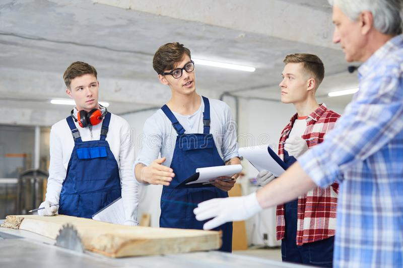 Young worker asking carpenter about wood processing royalty free stock photos