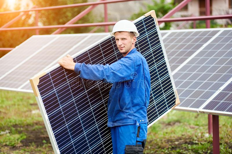 Installation of stand-alone exterior photo voltaic panels system. Renewable green energy generation. Young worker in blue uniform and protective helmet carrying stock photography