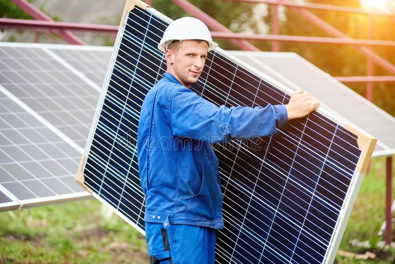 Installation of stand-alone exterior photo voltaic panels system. Renewable green energy generation. Young worker in blue uniform and protective helmet carrying stock photos