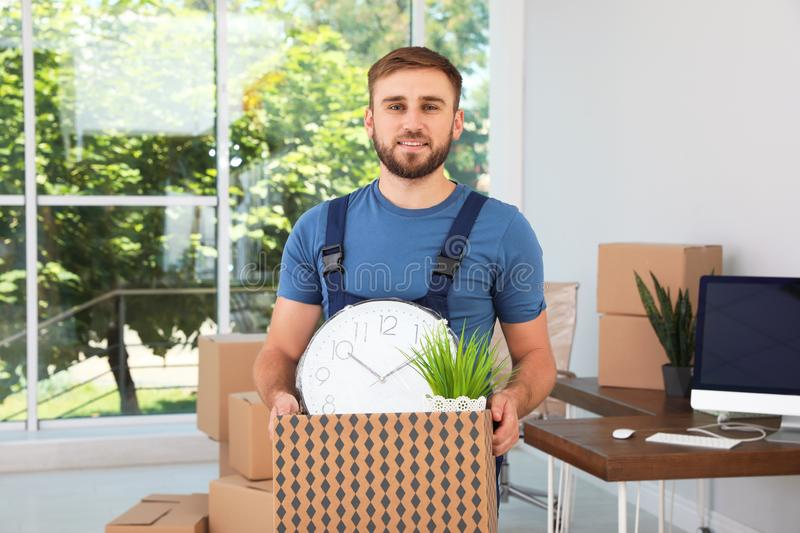 Young worker with box of things. Moving service royalty free stock images