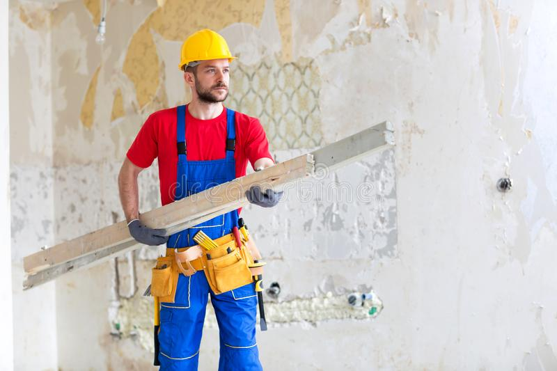 Young worker carrying wooden planks stock images