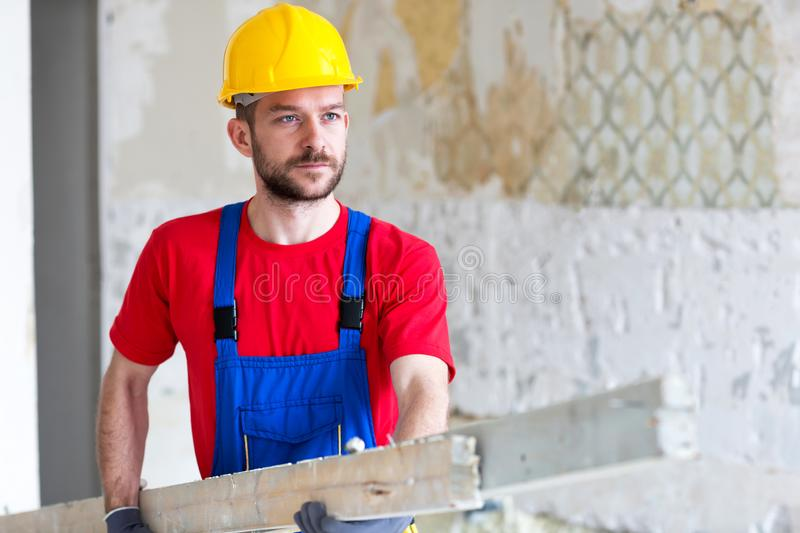 Young worker carrying wooden planks stock photo