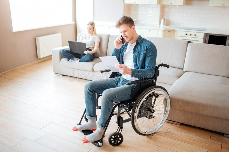 Young worker with disability in room. Holding piece of paper and talking on phone. Young woman sit behind on couch with stock images