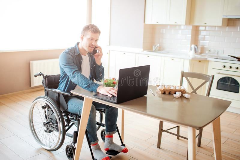 Young worker with disability and special needs sit at table and work. He use laptop and talk on phone. Alone in kitchen royalty free stock image