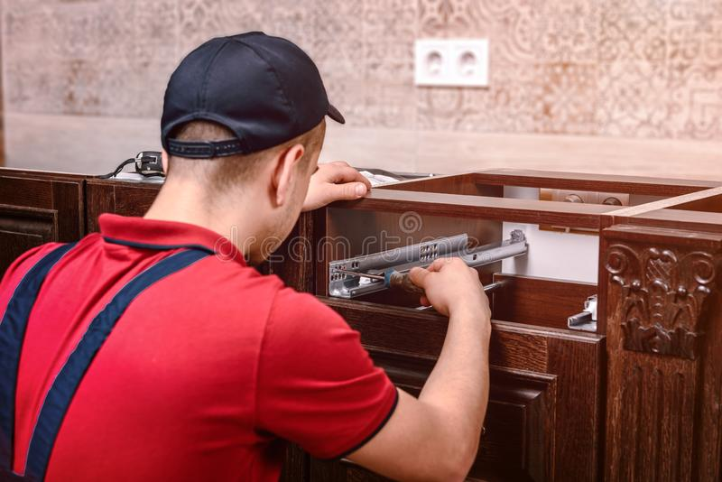 A young worker installs a drawer. Installation of modern wooden kitchen furniture stock photos
