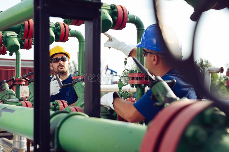 Worker on oil pump looks at laptop and speaking in a radio station. Young Worker on oil pump looks at laptop and speaking in a radio station stock photo