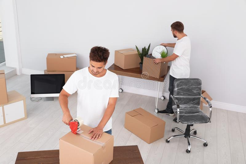 Young worker packing box and his colleague. Moving service stock image