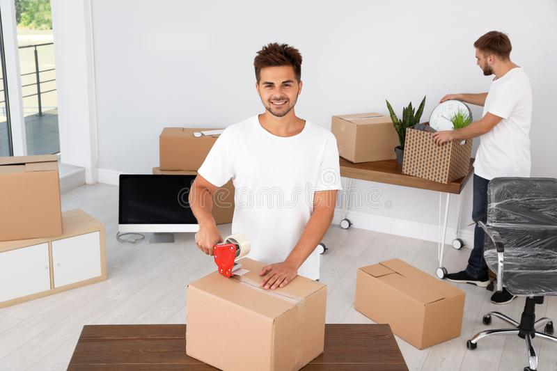 Young worker packing box and his  in office. Moving service royalty free stock photo