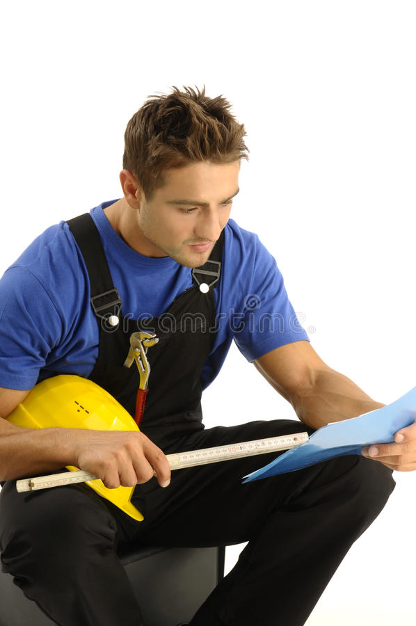 Young worker reading instructions. Manual worker studying his instructions stock image