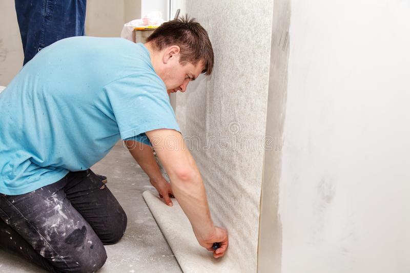 Young worker smoothing wallpaper in the room. Young worker smoothing wallpaper in his new own home closeup royalty free stock photos