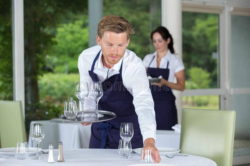 Young worker table setting. Setting royalty free stock image