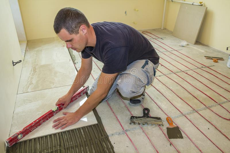 Young worker tiler installing ceramic tiles using lever on cement floor with heating red electrical cable wire system. Home royalty free stock photo