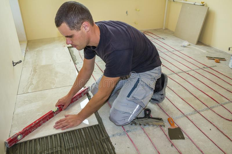 Young worker tiler installing ceramic tiles using lever on cement floor with heating red electrical cable wire system. Home royalty free stock photos