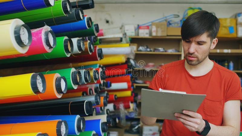 Young worker in warehouse with clipboard checking inventory. Man works in sales department of advertising materials. Young worker in warehouse with clipboard stock photography
