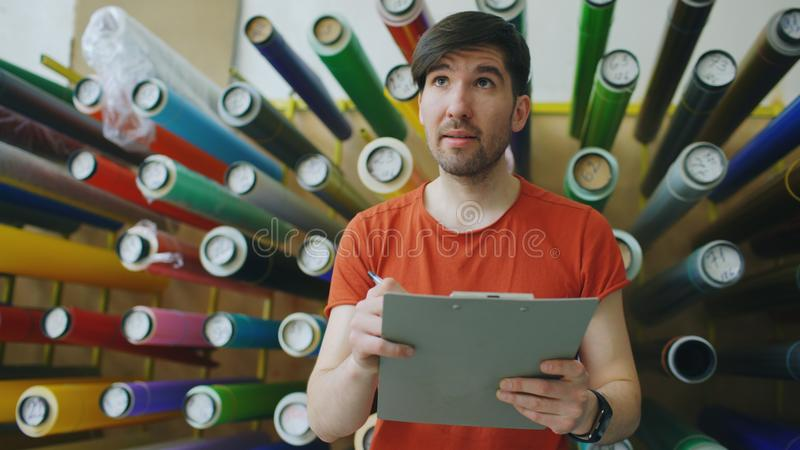Young worker in warehouse with clipboard checking inventory. Man works in sales department of advertising materials. Young worker in warehouse with clipboard stock image
