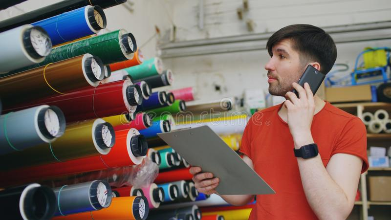 Young worker in warehouse talking smartphone and checking inventory. Man works in sales department of advertising. Material royalty free stock photography