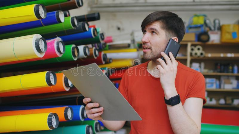 Young worker in warehouse talking smartphone and checking inventory. Man works in sales department of advertising. Material royalty free stock image