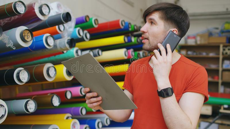 Young worker in warehouse talking smartphone and checking inventory. Man works in sales department of advertising. Material stock image