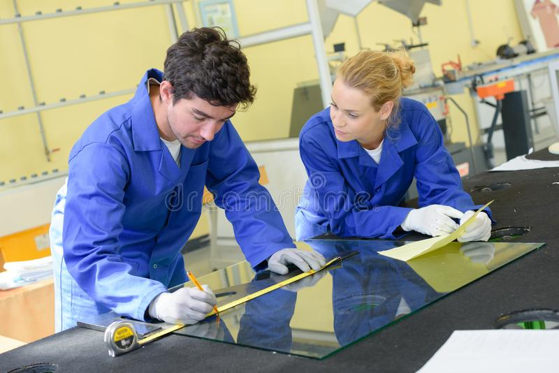 Young workers measuring pane glass stock photography
