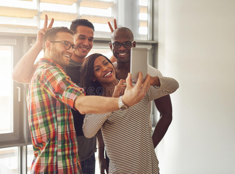 Young workers taking self portrait with phone. Diverse group of happy young workers taking pictures and making symbolic hand gestures for camera phone at small stock photography