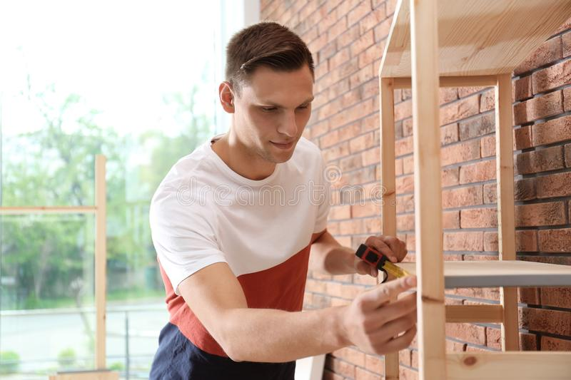 Young working man measuring wooden shelf stock photography